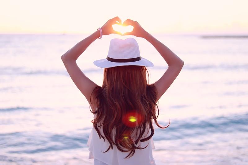 海に落ちて行く夕陽にハートの手をかざす女の子