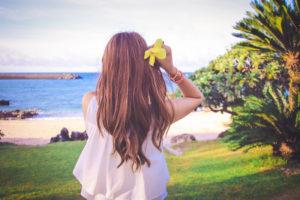 リゾートビーチで南国の黄色い花を髪にさしている女の子