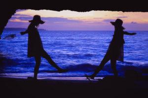 夕暮れの海をバックにじゃれあっている双子の女の子たち